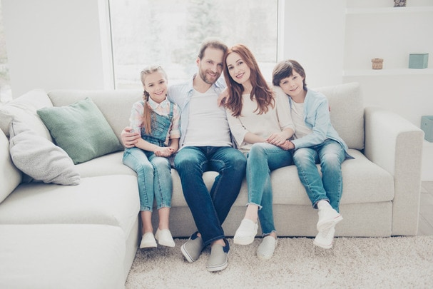 Couple sitting on sofa with children
