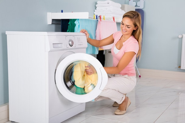 Woman Loading Dirty Clothes In Washing Machine